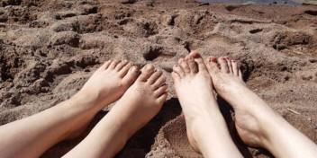 Liljaaksolaisia hiekkarannalla paljain varpain.