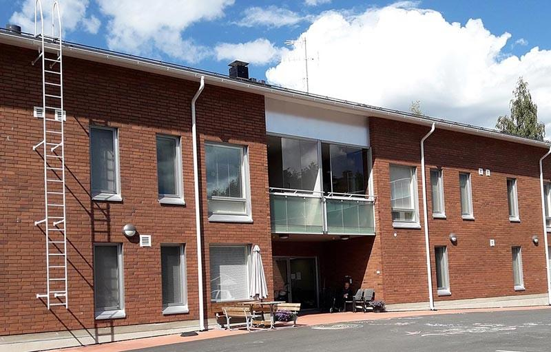Aspa-koti Kotiharju sijaitsee kaksikerroksisessa rakennuksessa Valtimon keskustassa.
