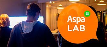 Ihmisiä, oranssissa puhekuplassa teksti AspaLAB.