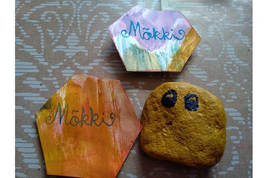 kaksi magneettia, joissa lukee mökki, sekä maalattu kivi.
